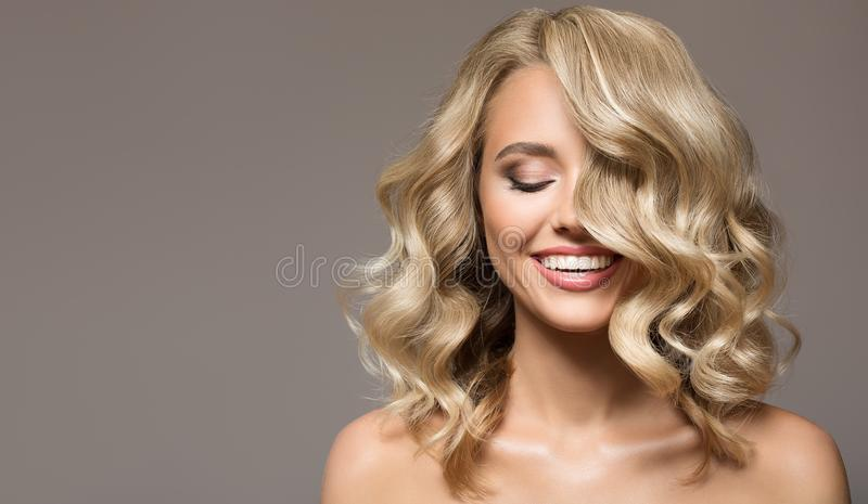 Blonde woman with curly beautiful hair smiling. On gray background