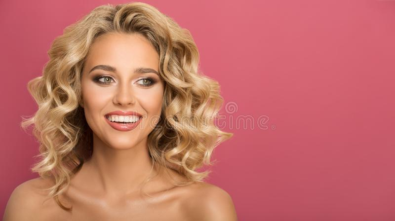 Blonde woman with curly beautiful hair smiling. On pink background royalty free stock photo