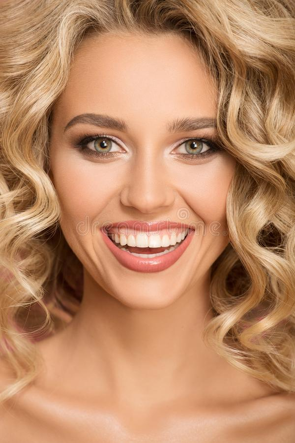 Blonde woman with curly beautiful hair smiling. Close up portrait royalty free stock photos