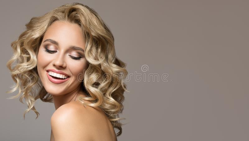 Blonde woman with curly beautiful hair smiling. On gray background stock image
