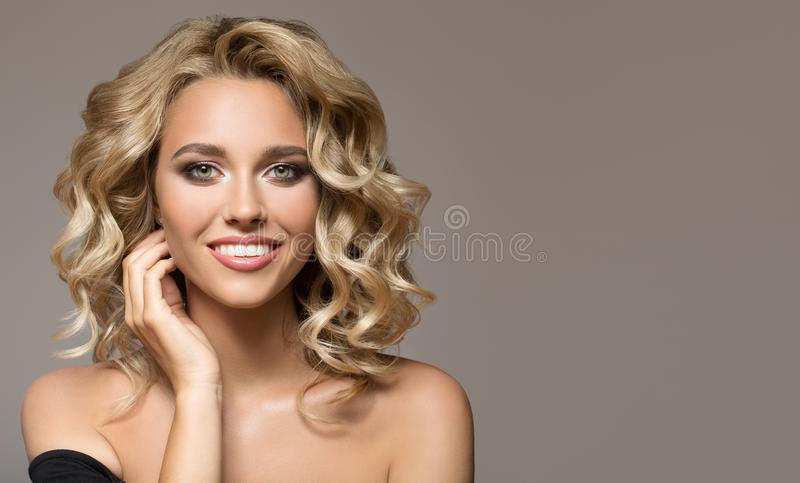 Blonde woman with curly beautiful hair smiling. On gray background royalty free stock photography