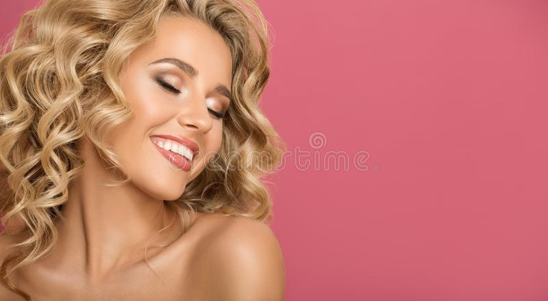 Blonde woman with curly beautiful hair smiling. On pink background stock image