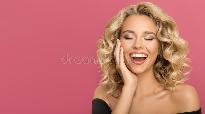 Blonde woman with curly beautiful hair smiling. On pink background royalty free stock image