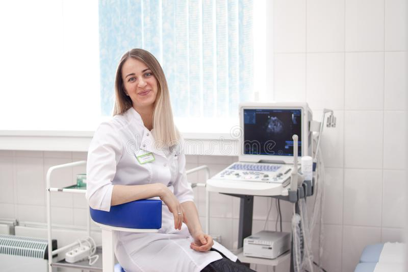 Blonde woman doctor in white uniform in clinic hospital works on ultrasound scanner and smiles at camera. Diagnostics. Sonography and health concept. copyspase royalty free stock photo