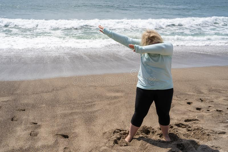 Blonde woman does a dabbing dance move on the beach stock image