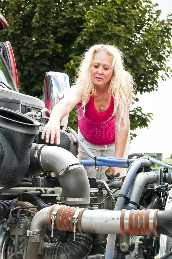 Blonde woman doing pretrip inspection. Adult woman truckdriver doing a pre-trip inspection on her truck before her run stock photos