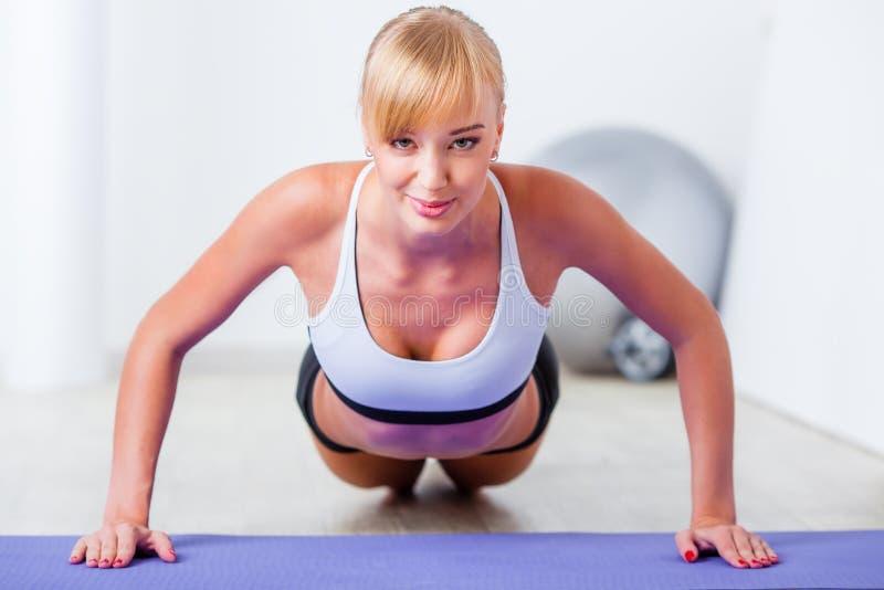 Blonde woman doing push-ups. On the mat stock photos