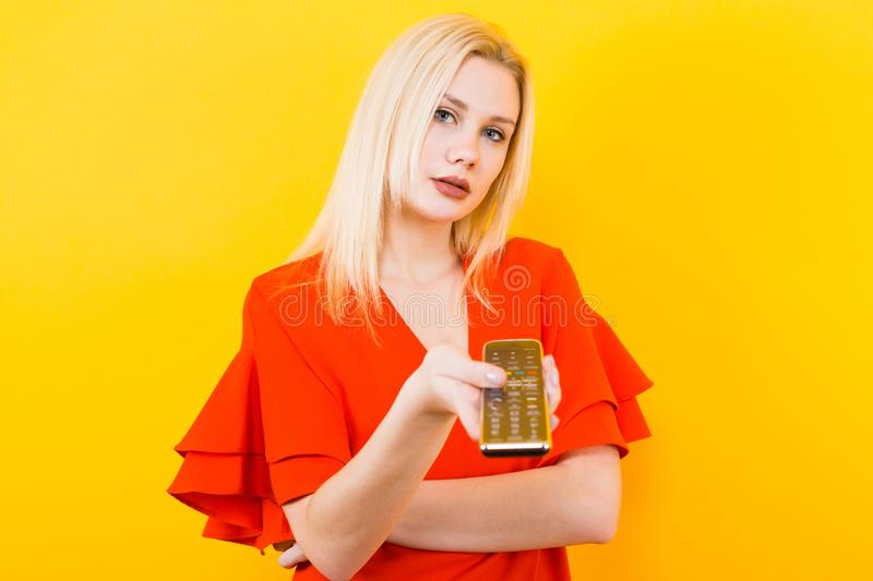 Blonde woman in dress with remote control royalty free stock photography