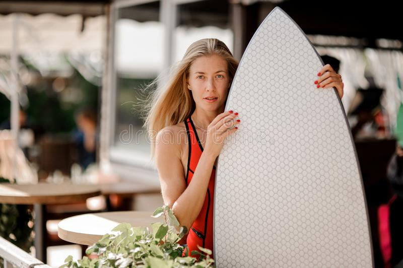 Blonde woman dressed in red swimsuit with a wakeboard. Young beautiful blonde woman dressed in red swimsuit with a wakeboard standing against the restaurant royalty free stock images