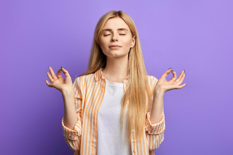 Blonde woman dressed in striped shirt and white T-shirt doing yoga stock photos