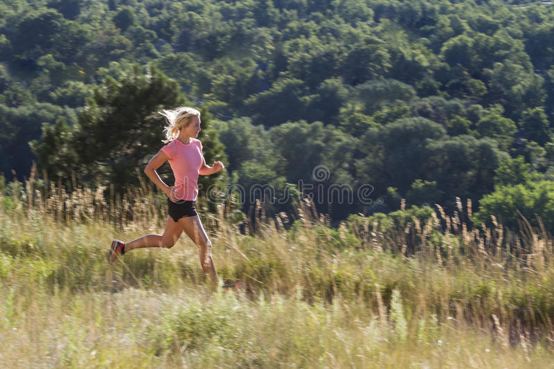 Blonde woman on early morning run with distant tree background. Woman on early morning run on grassy trail with beautiful back light and distant trees stock images