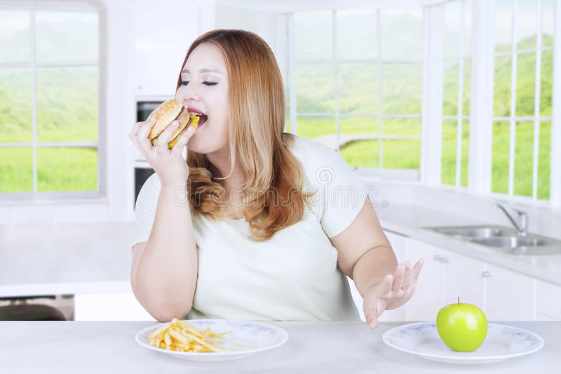 Blonde woman eating burger in kitchen. Blonde woman choosing to eat hamburger and refusing a fresh apple fruit in the kitchen stock photography