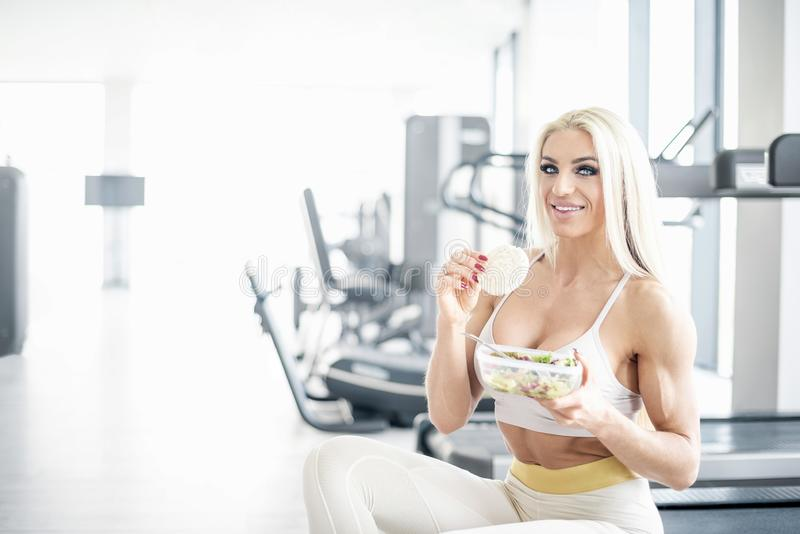 Blonde woman eating healthy in gym stock image