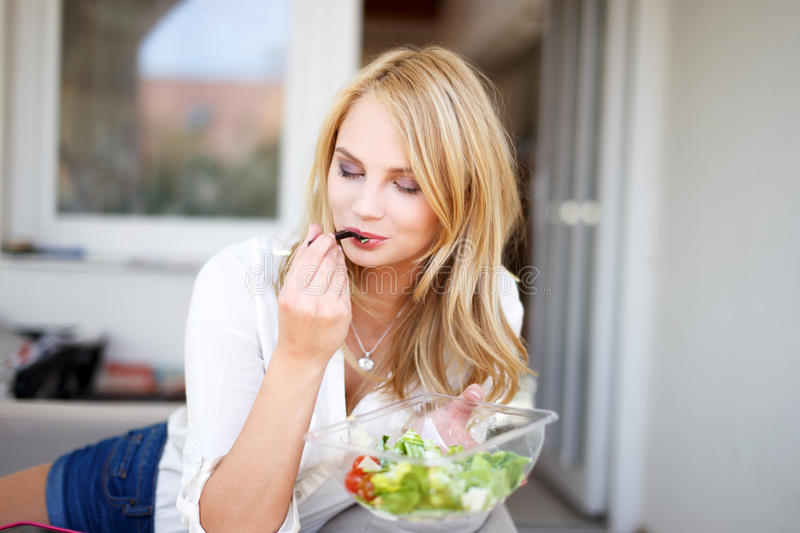Blonde woman eating salad outdoor royalty free stock photo
