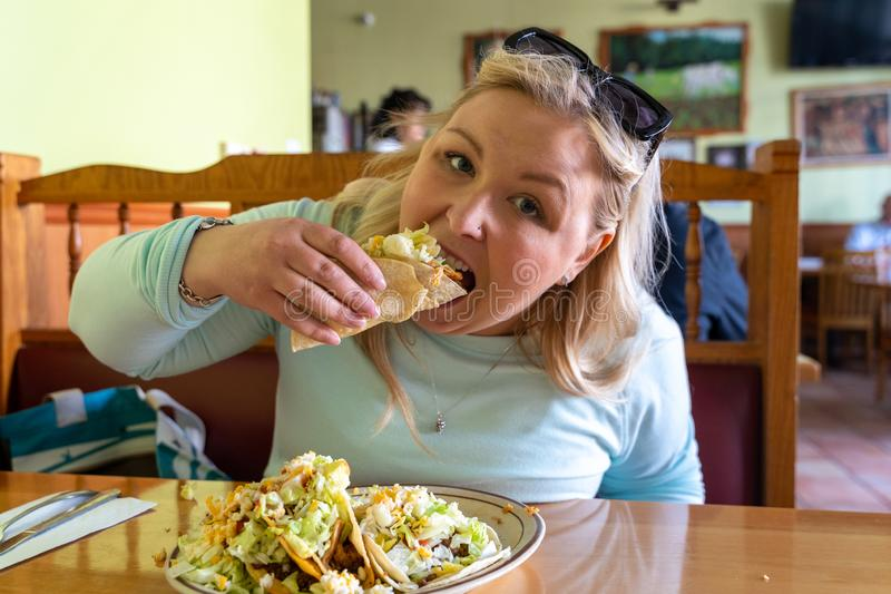 Blonde woman eats a plate of tacos inside of a Mexican restaurant, enjoying her meal royalty free stock image