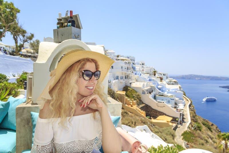 Blonde woman enjoying the view of greek town Thira in Santorini, Greece stock photography