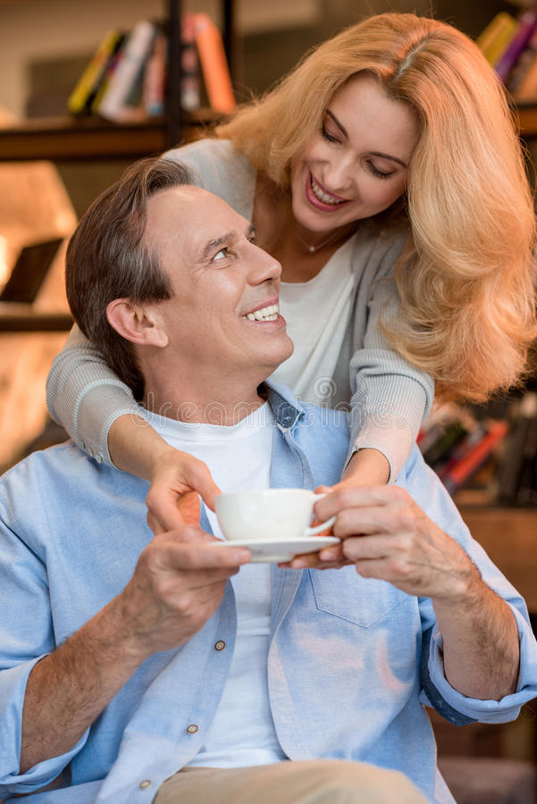 Blonde woman giving tea cup to happy mature man stock image