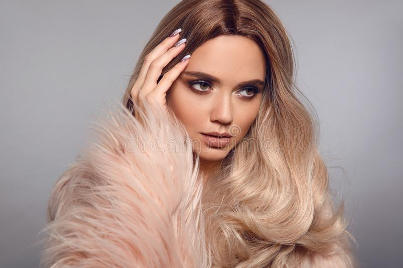 Blonde woman in glamorous fur coat posing in studio. Ombre blond hairstyle. Beauty fashion girl portrait. Beautiful model with royalty free stock photography