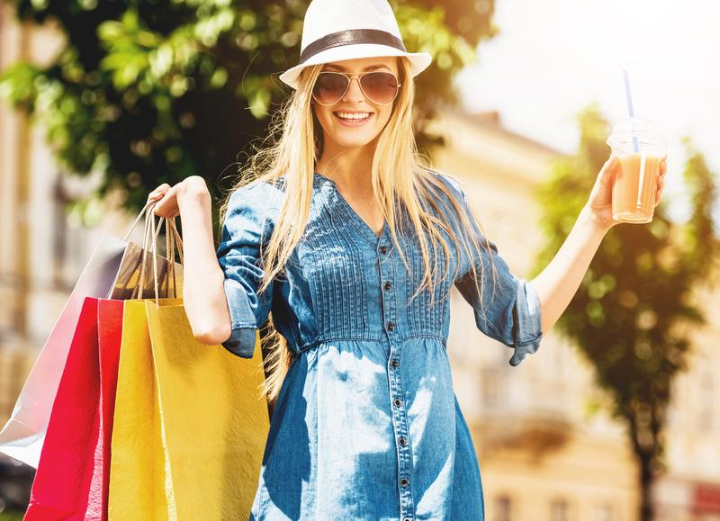 Blonde Woman with Glass of Juice After Shopping. Reducing Stress by Buying. Carefree Summer. Beautiful Happy Cute Young Girl with Multicolored Shopping Bags royalty free stock photo