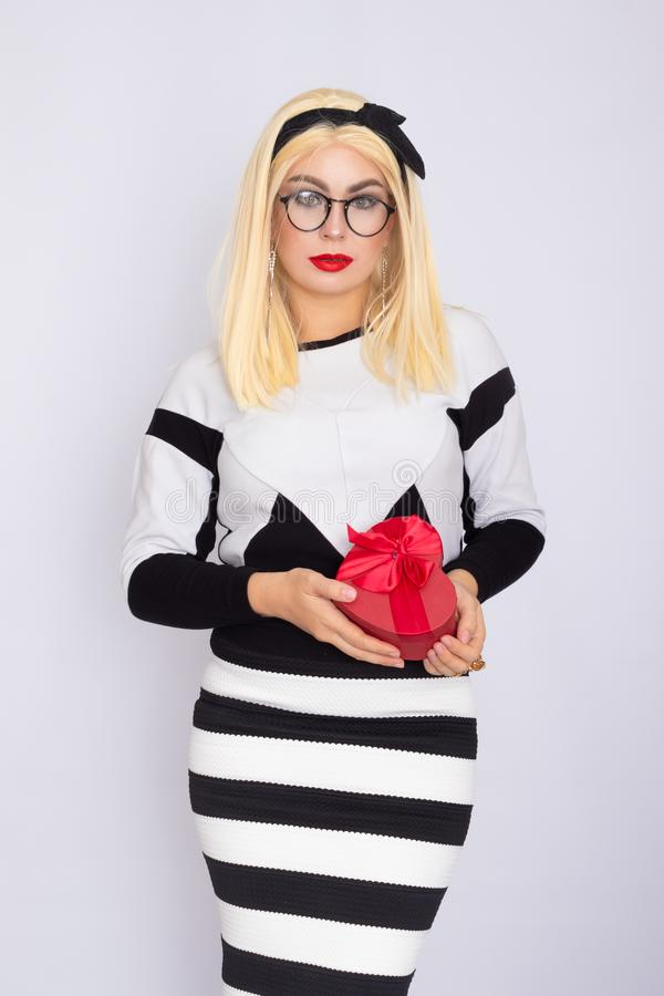 Blonde woman in glasses holding heart gift box in her hands royalty free stock images