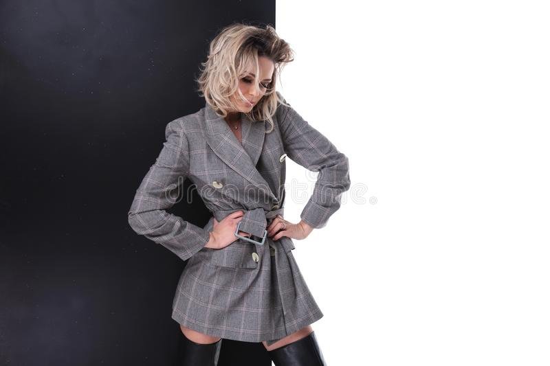 Blonde woman in grey checkered suit posing while holding hips royalty free stock photo
