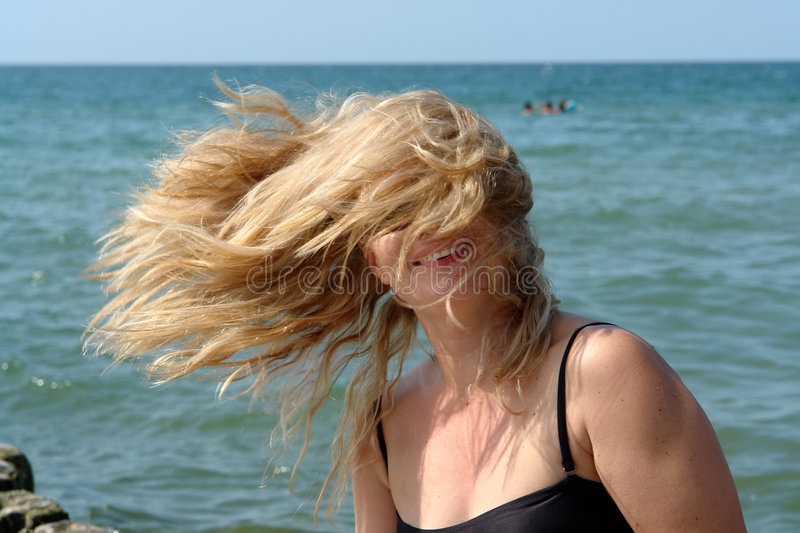 Blonde woman, hair in the air, covering the face. stock photos