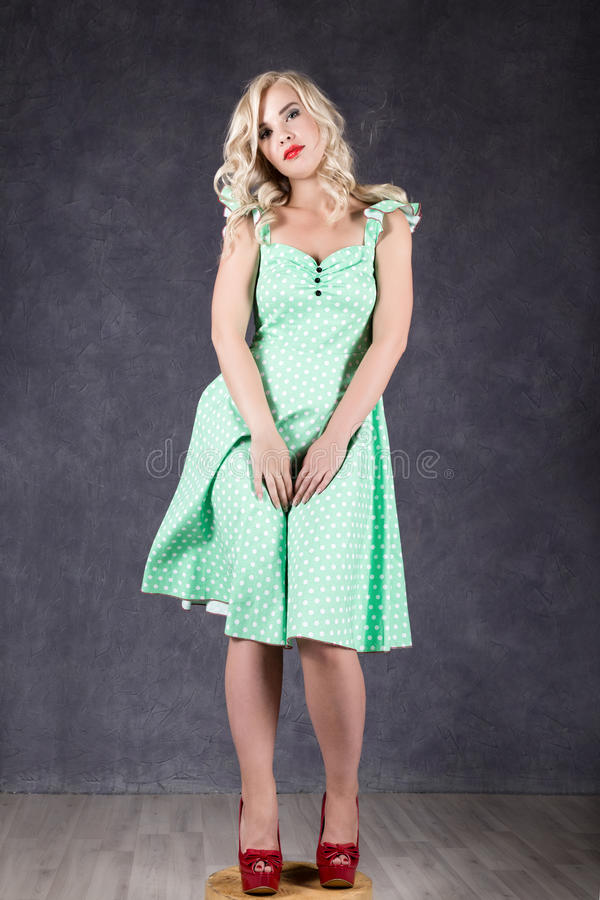 Blonde woman with hair in the wind. girl with flying hair posing in green dress and red shoes stock photos