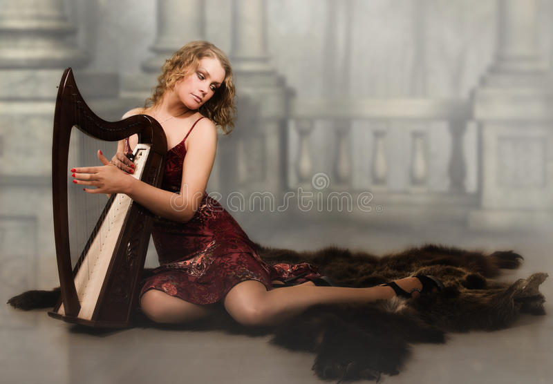Blonde woman with a harp in his hand royalty free stock photo