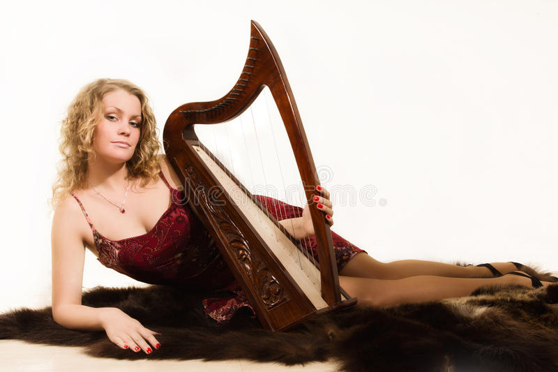 Blonde woman with a harp in his hand royalty free stock images