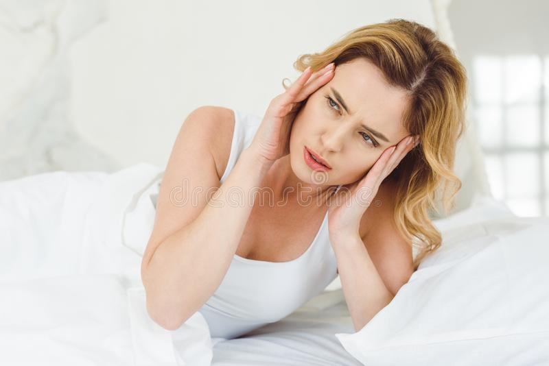 blonde woman having headache and lying in bed stock photography