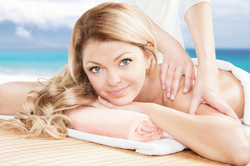 Blonde woman having a professional massage on the beach. Looking at the camera and smiling. Beautiful young women relaxing with hand massage at spa royalty free stock images