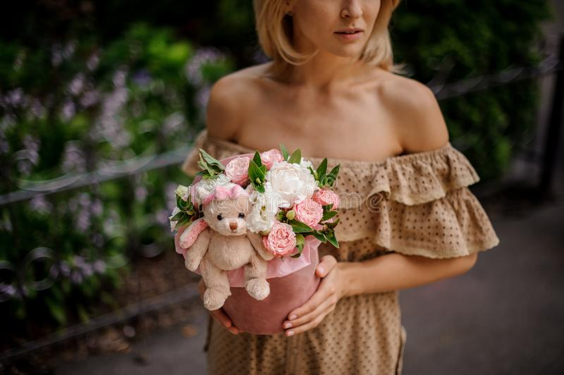 Blonde woman holding a box filled with flowers stock images