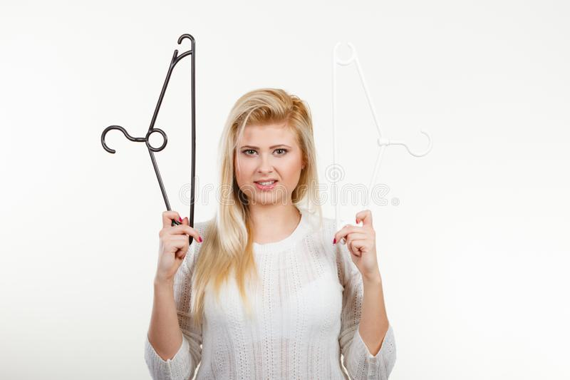 Blonde woman holding clothes hanger royalty free stock image