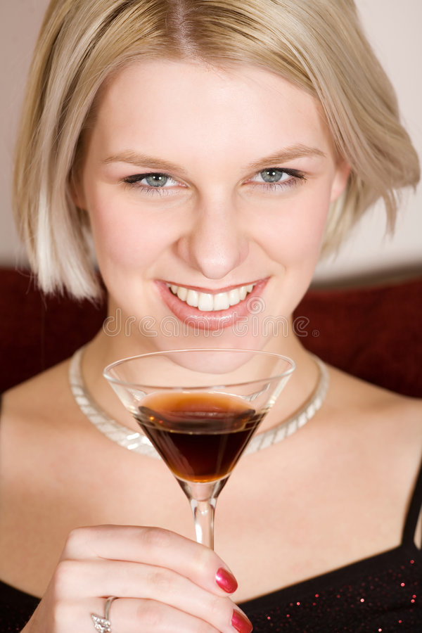 Blonde woman holding a cocktail glass