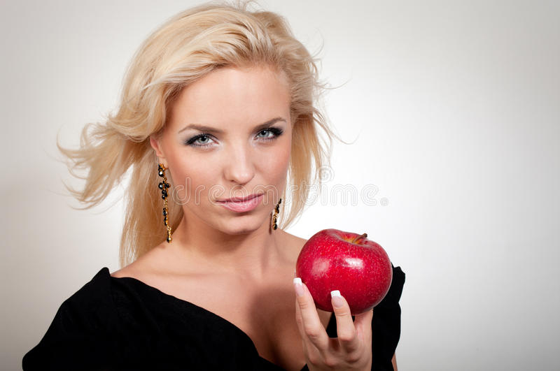 Blonde woman holding red apple stock photo