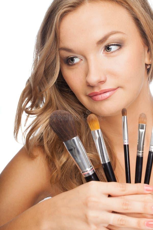Blonde woman holding set of brushes royalty free stock photo