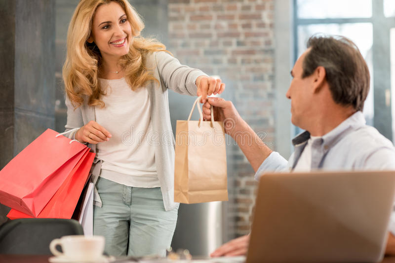 Blonde woman holding shopping bags and giving paper bag to husband at home royalty free stock photography