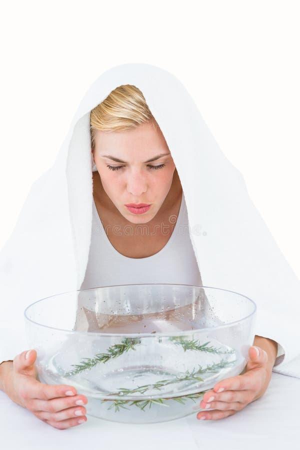Blonde woman inhaling herbal medicine royalty free stock photos