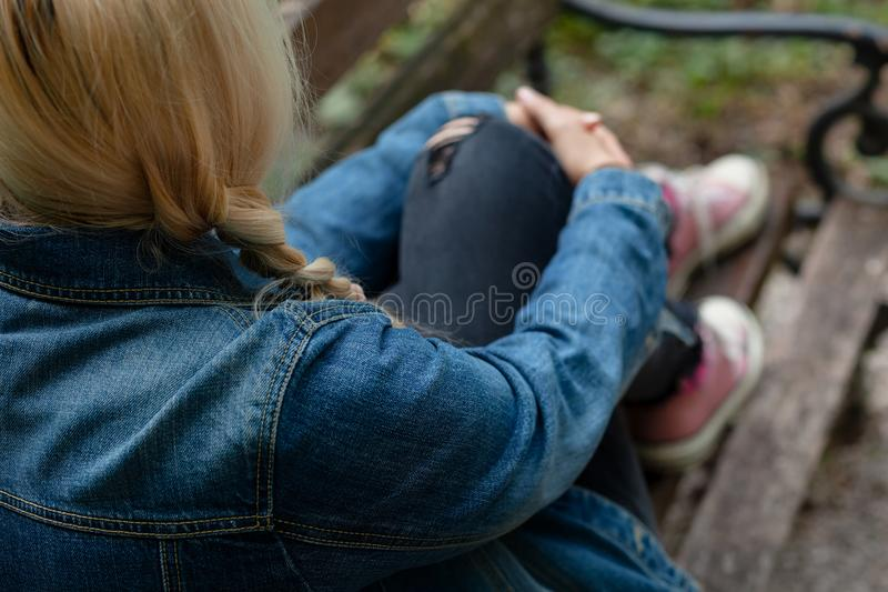 Blonde woman in jeans jacket sitting alone on a park bench, holding her leg stock images