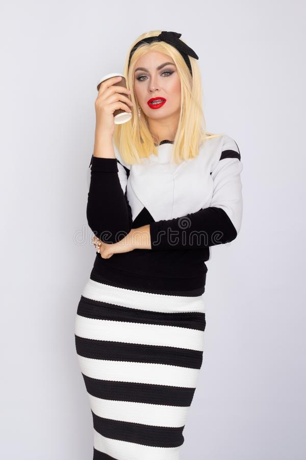 Blonde woman in knitted costume holding cup with hot coffee in her hands royalty free stock photography