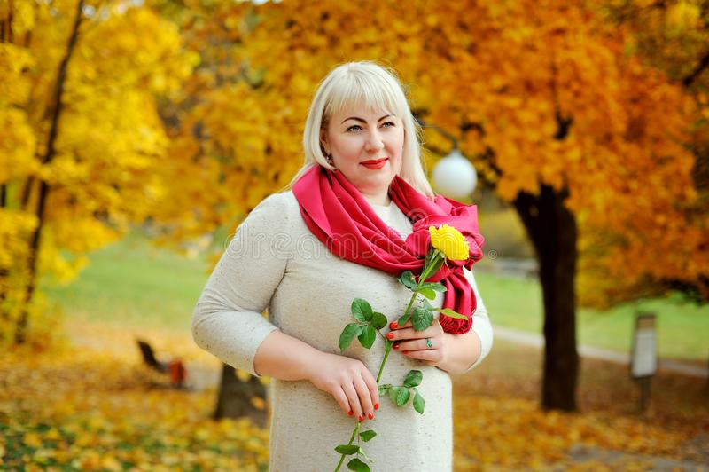 Blonde woman of large size in the Park, outdoors. She stands and poses with a yellow rose in her hand, wearing a red royalty free stock photos