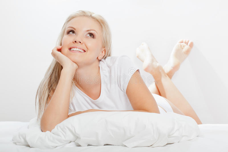 Blonde woman laying on bed stock photo
