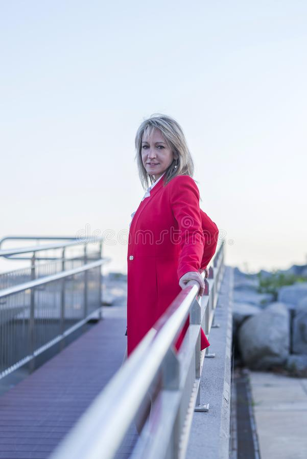 Blonde woman leaning on a metallic fence on a runaway. Blonde elegant woman wearing red jacket leaning on a metallic fence on a runaway stock photos