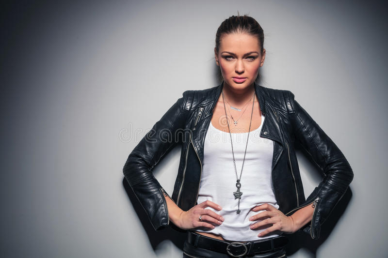 Blonde woman in leather jacket holding hands on waist royalty free stock images