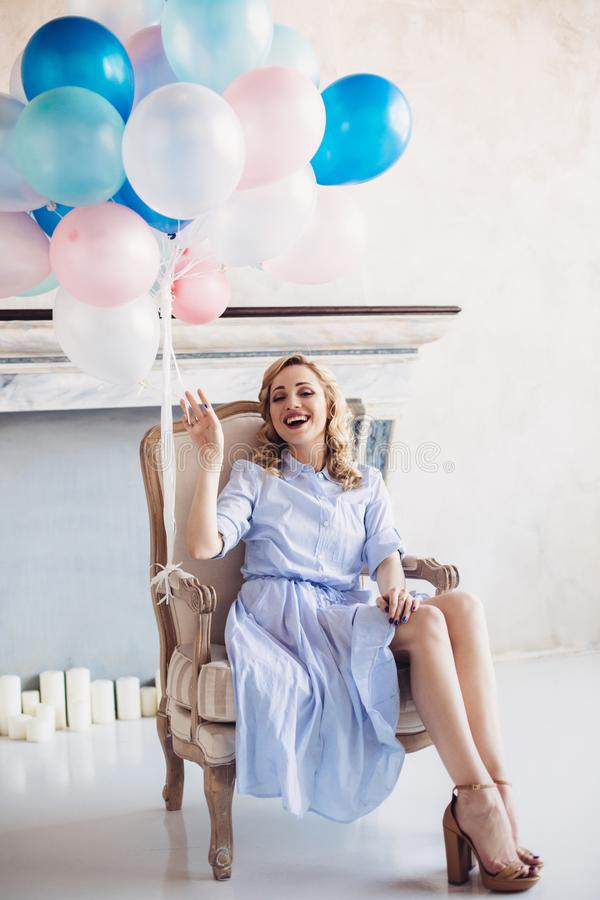 Blonde woman with balloons sit in chair royalty free stock images