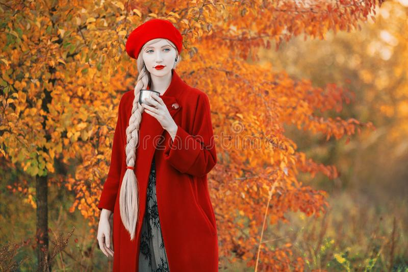 Blonde woman with long hair in red coat on autumn background. Girl drink tea from thermos cup on background of forest with orange. Autumn leaves. Leaves fall royalty free stock images