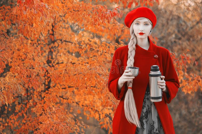 Blonde woman with long hair in red coat on autumn background. Girl drink tea from thermos cup on background of forest with orange stock photo