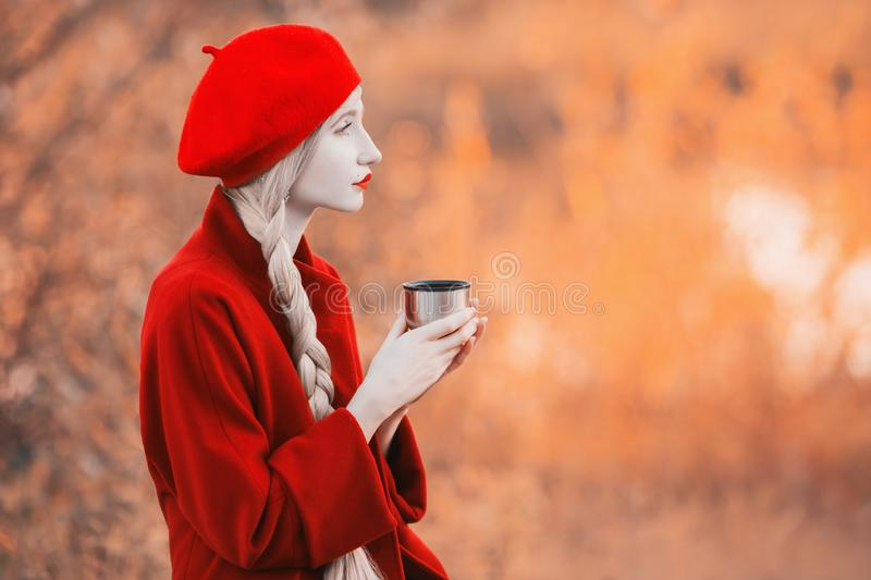 Blonde woman with long hair in red coat on autumn background. Girl drink tea from thermos cup on background of forest with orange stock photos