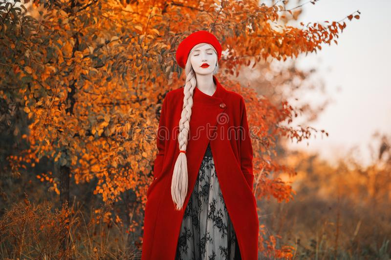 Blonde woman with long hair in red coat on autumn background. Girl with long braided plait on background of forest with orange. Autumn leaves. Leaves fall from royalty free stock image