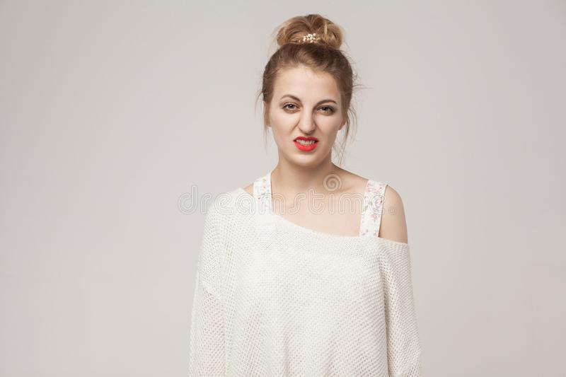 Blonde woman looking at camera with disgust. Studio shot, gray wall royalty free stock photos